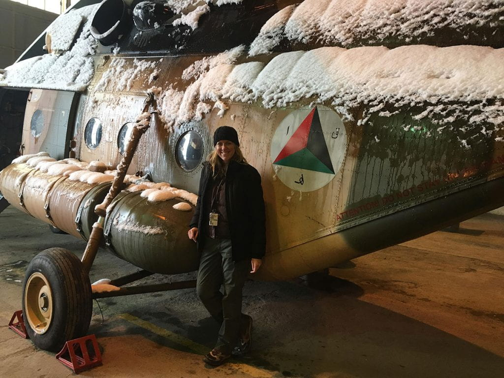Laurie Hart '03 leans against an MI-17 helicopter in Afghanistan, where she instructed MI-17 mechanics in English.