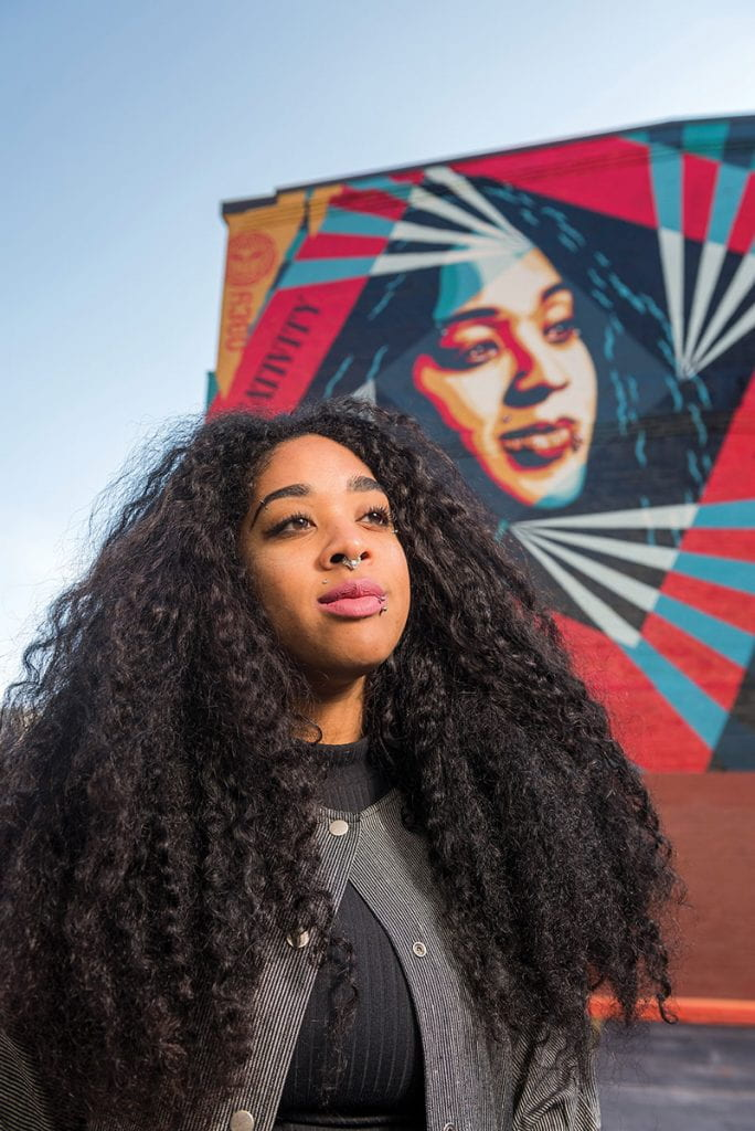 Anjel Newmann in front of the Shepard Fairey mural in Providence