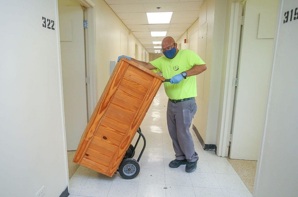 Furniture is removed from a room in Aquinas Hall to allow floors to be sterilized.