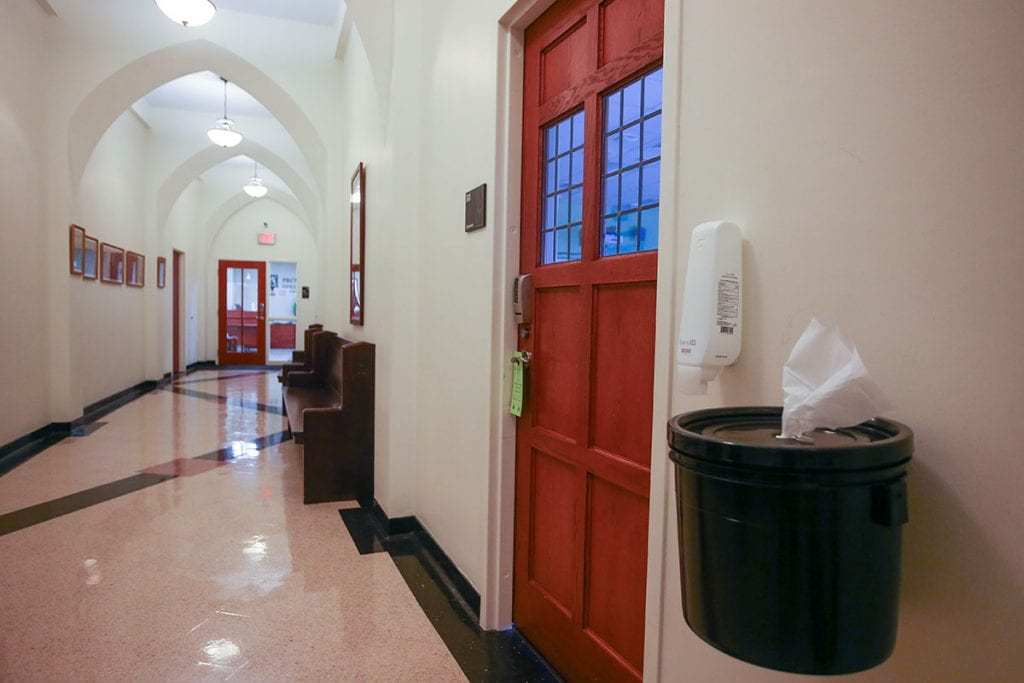 Hand sanitizer and paper towels are available outside a classroom on the third floor of Harkins Hall.