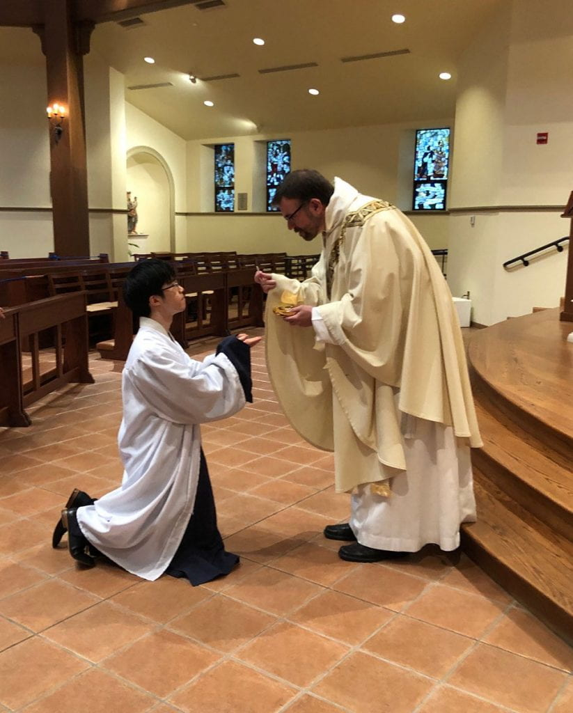 Tianyi Yuan '20 receives the Eucharist for the first time during an RCIA Mass in St. Dominic Chapel before beginning his studies at Harvard Divinity School. The priest is Rev. Jordan Zajac, O.P. '04.