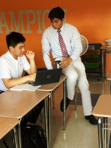 A Pact teacher and student discussing the contents of a laptop screen at a classroom table