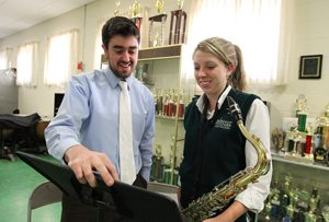 A Pact teacher and a student with a saxophone looking at some sheet music