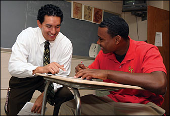 a pact teacher working with a student wearing a red shirt