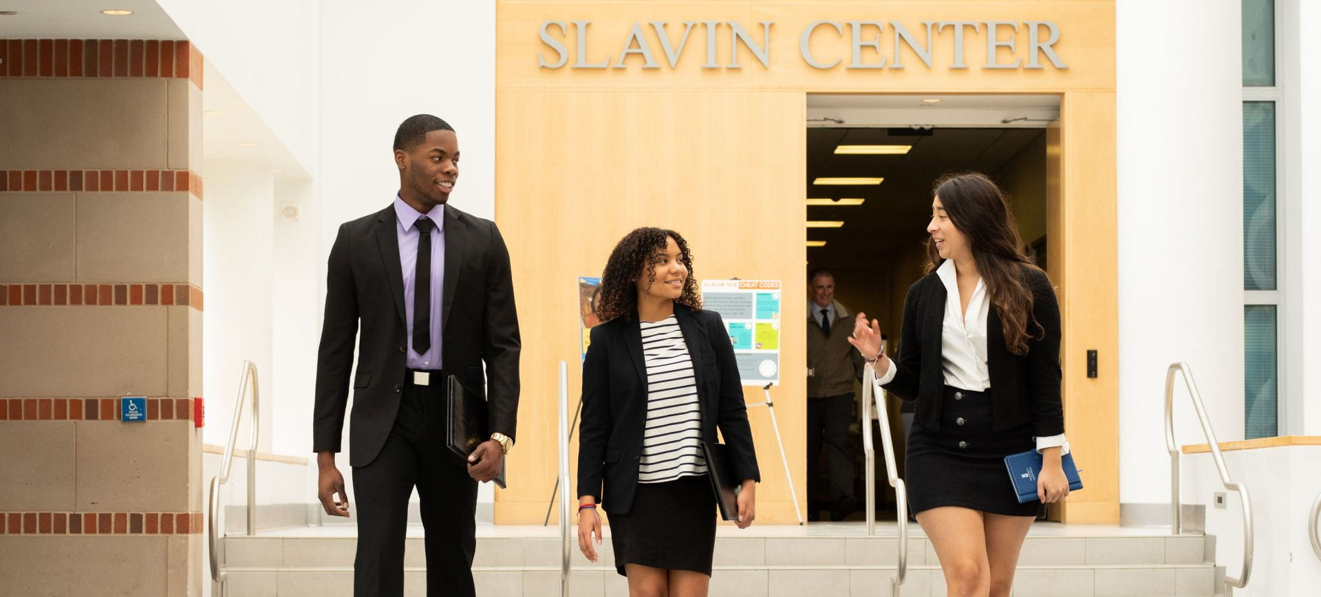three students in suits walking in atrium