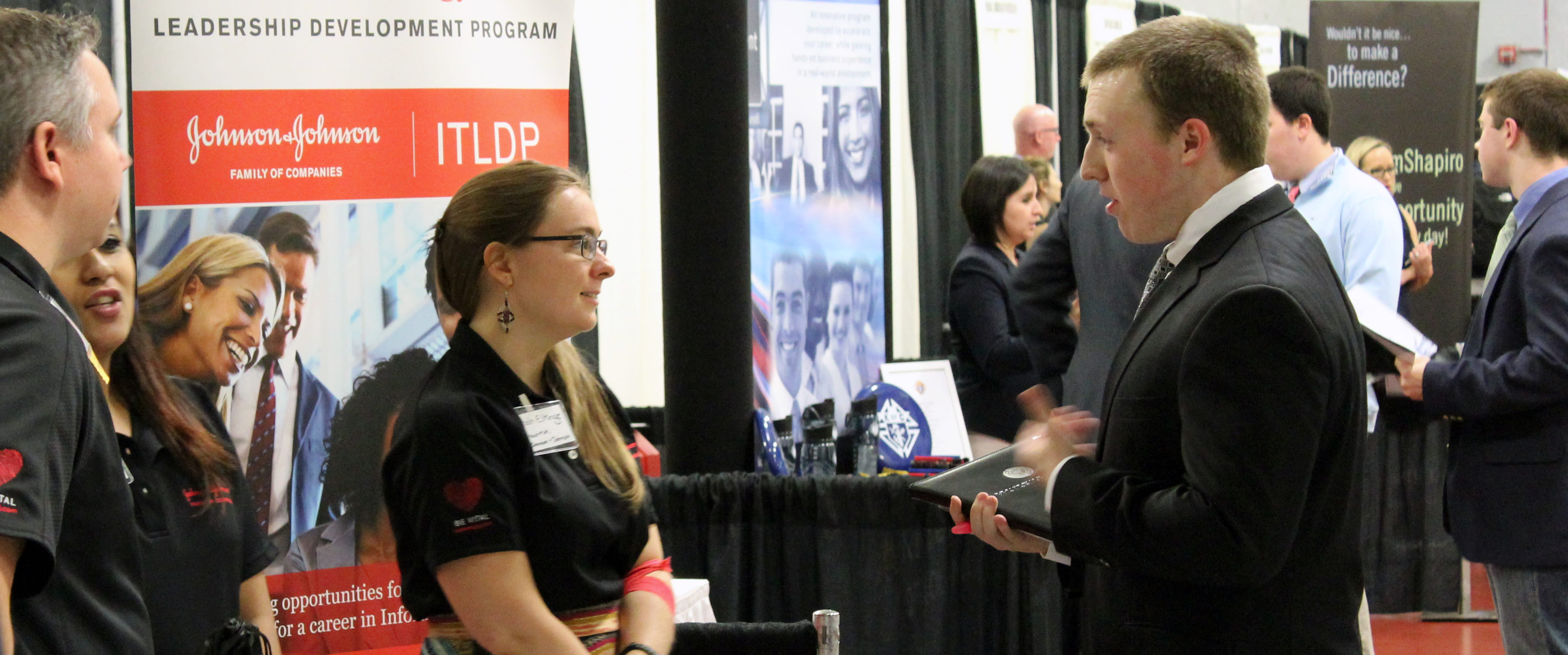 student in suit at career expo talking to recruiter about leadership development program