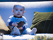 Baby on sofa with television remote