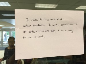 An index card taped to a wall outside Lubert Commons expressing one participant's feelings on the writing process.