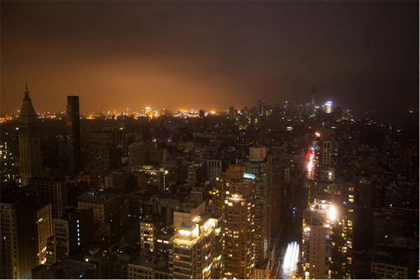 Night scene of Manhattan, New York City, with a large section of the cityscape without lights.