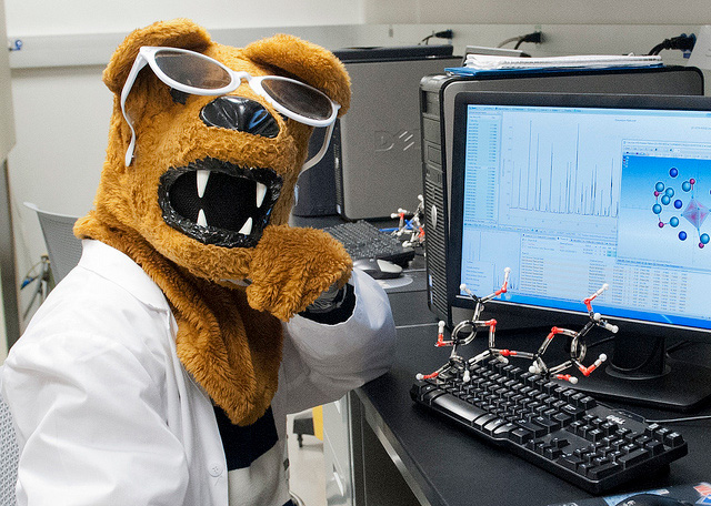 Penn State Nittany Lion in a lab coat, sitting at a computer.