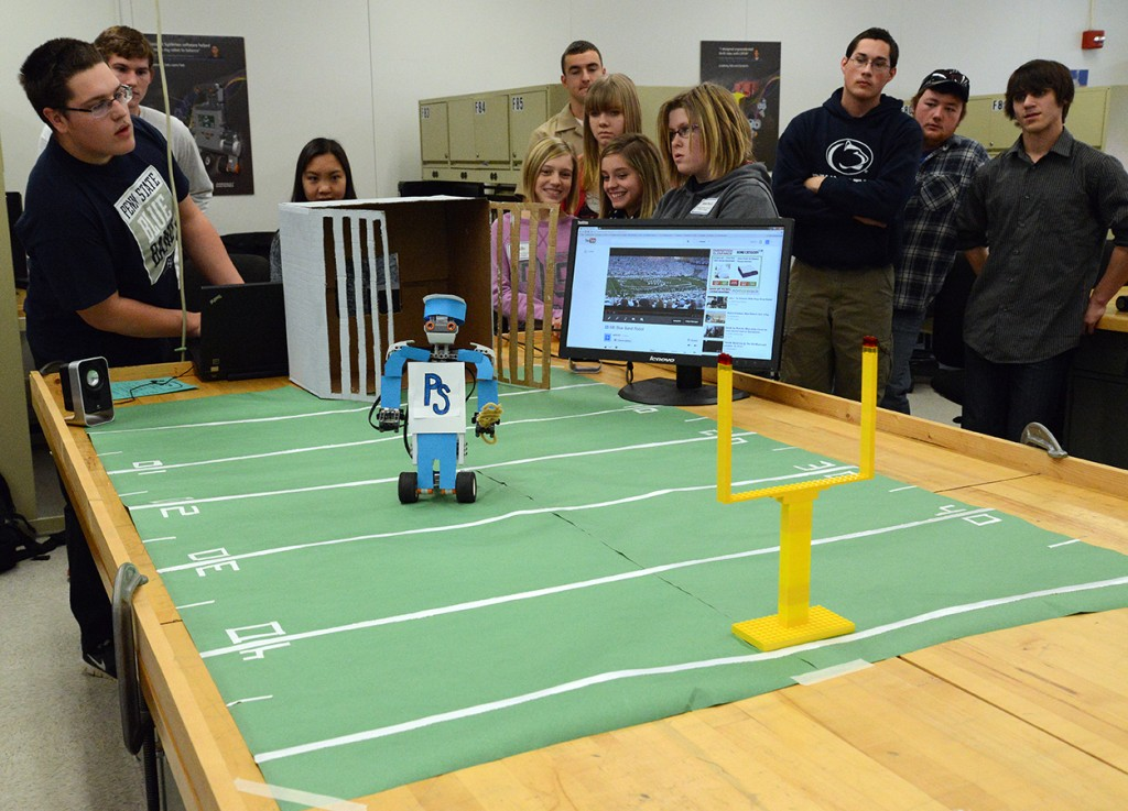 Girls from two area middle schools teamed with Penn State engineering students to program robotic dance routines as part of their field trip to campus. One project had a Blue Band theme with a robotic drum major. (Photo credit: Curtis Chan)