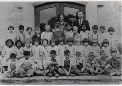 First grade class in 1929 seated outside of school with teacher Xenia Voigt