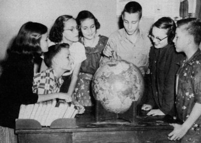 Six students looking at round globe.