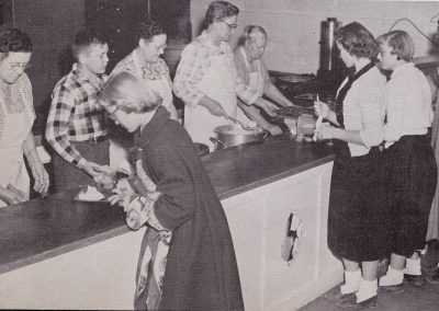 Lunch line showing six women and one younger male student serving food from pots to two female students