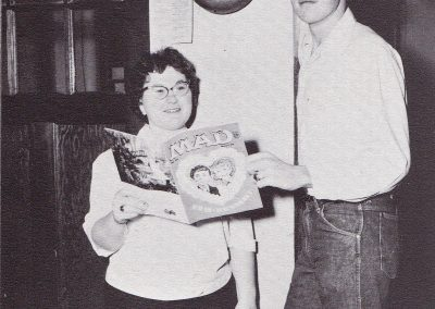Female and male student standing in front of office both are holding a single issue of Mad Magazine. The boy is significantly taller and has his finger on the fire alarm lever.