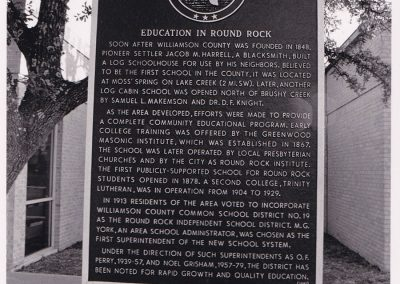 Historical marker providing a historical summary of Education in Round Rock. The black rectangular sign is set in the ground and a tree and a light brick building is in the background