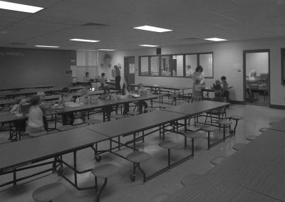 Black and white photo of Robertson Elementary. One table is being used by students. Teacher is helping two students near line.