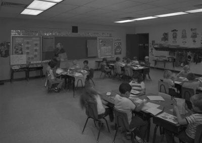Inside view of elementary classroom with students seated at desks. A teacher is standing at the front of the class.