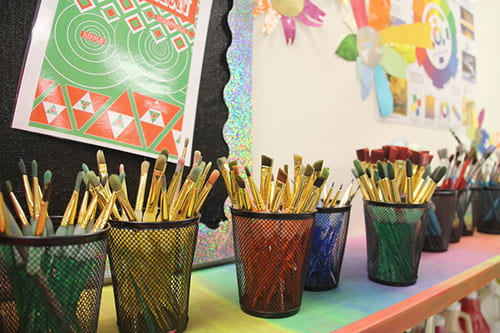 Multiple wire containers holding paint brushes. They are on a shelf against a wall in a classroom setting.