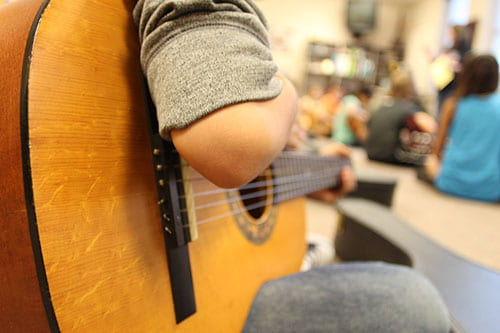 close up of student playing guitar