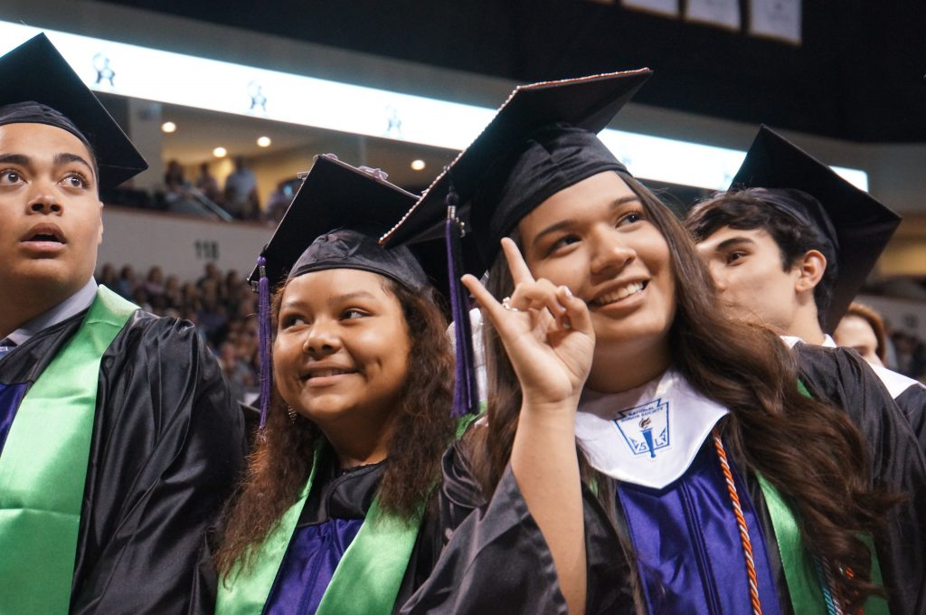 "McNeil graduate wearing cap and gown and flashing ""Hook Em"" hand signal"