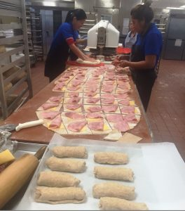 photo of cafeteria staff assembling ham and cheese burritos