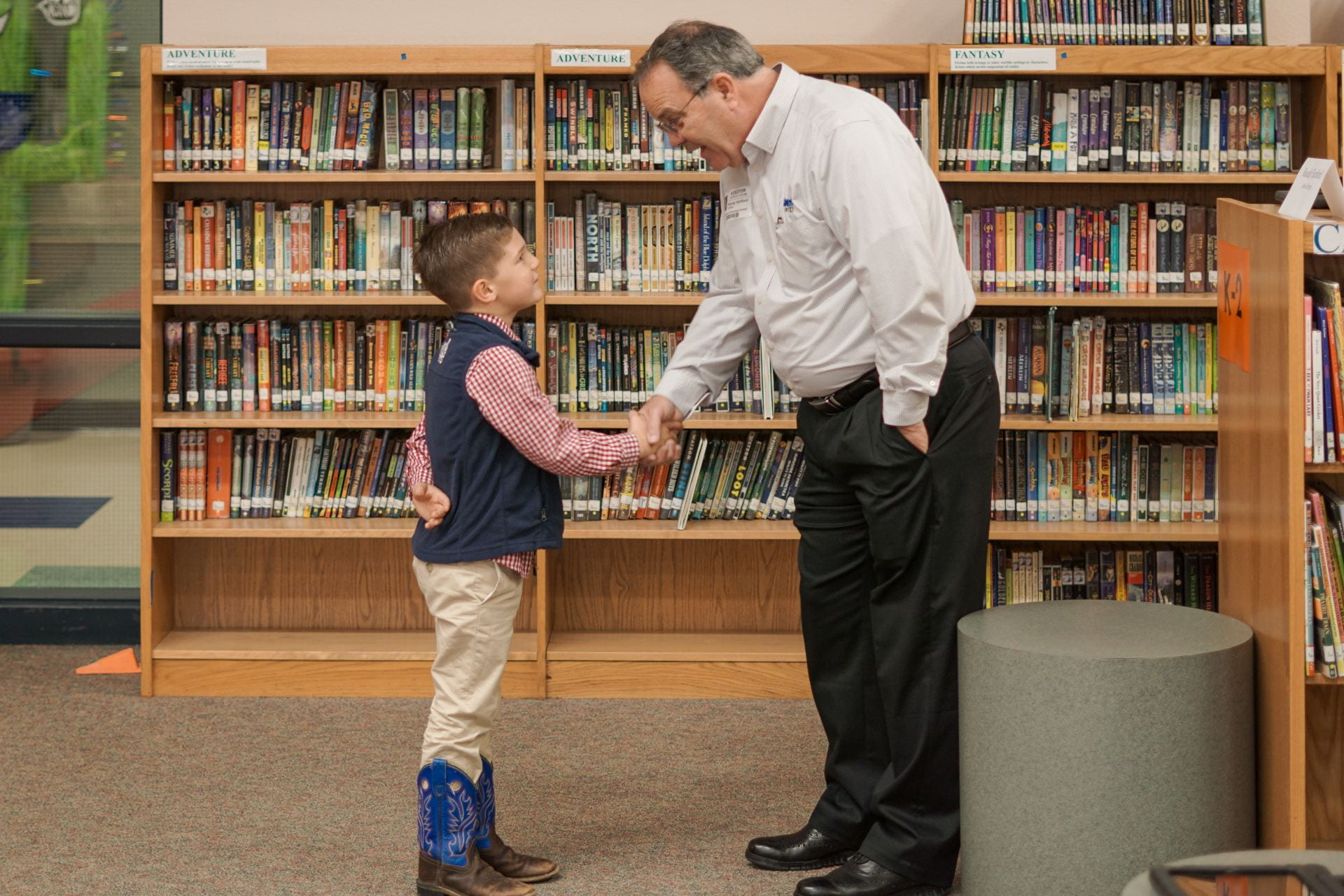 Community volunteer shaking hands with a student in a library