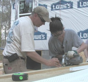 Tom teaches Jess how to cut a straight line with a power saw.