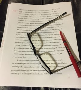 An essay, glasses and a red pen
