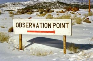 """a sign which reads """"observation point"""" with a red arrow against the backdrop of a snowy mountain landscape"""