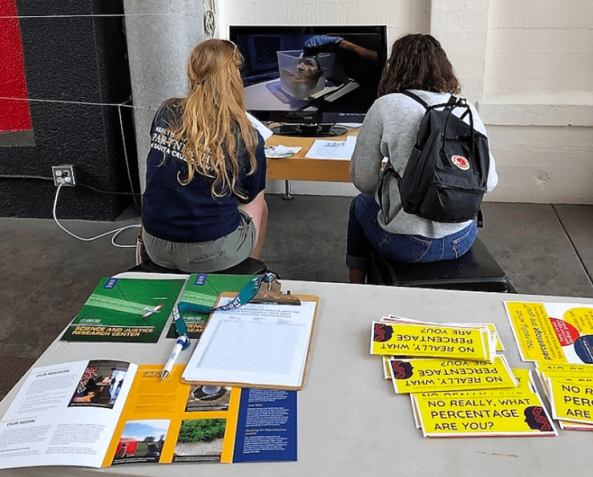 Two people watch the tv screen, a table is in view with information pamphlets.