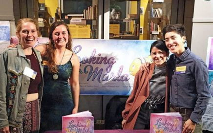 People standing behind a table with copies of Looking for Marla.