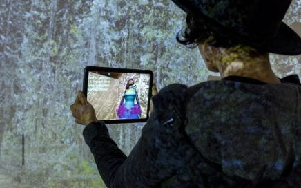 screenshot of game character holding a digital device showing another game character.