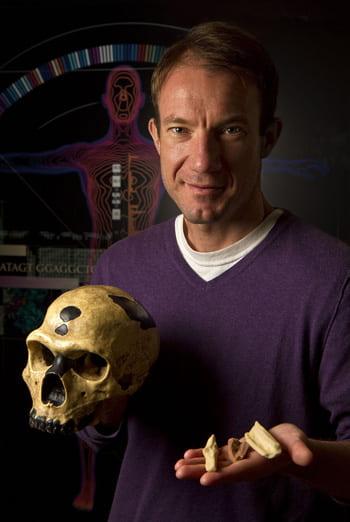 Portrait of UC Santa Cruz Genomics Institute's Richard (Ed) Green holding a Neanderthal skull and bones