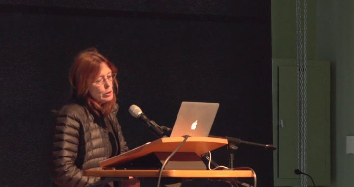 Carla Freccero is shown giving a talk, with a laptop and microphone.