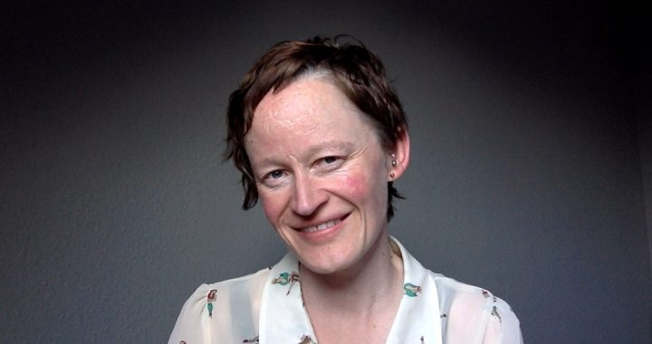A portrait of Carrie Smith is shown against a grey backdrop