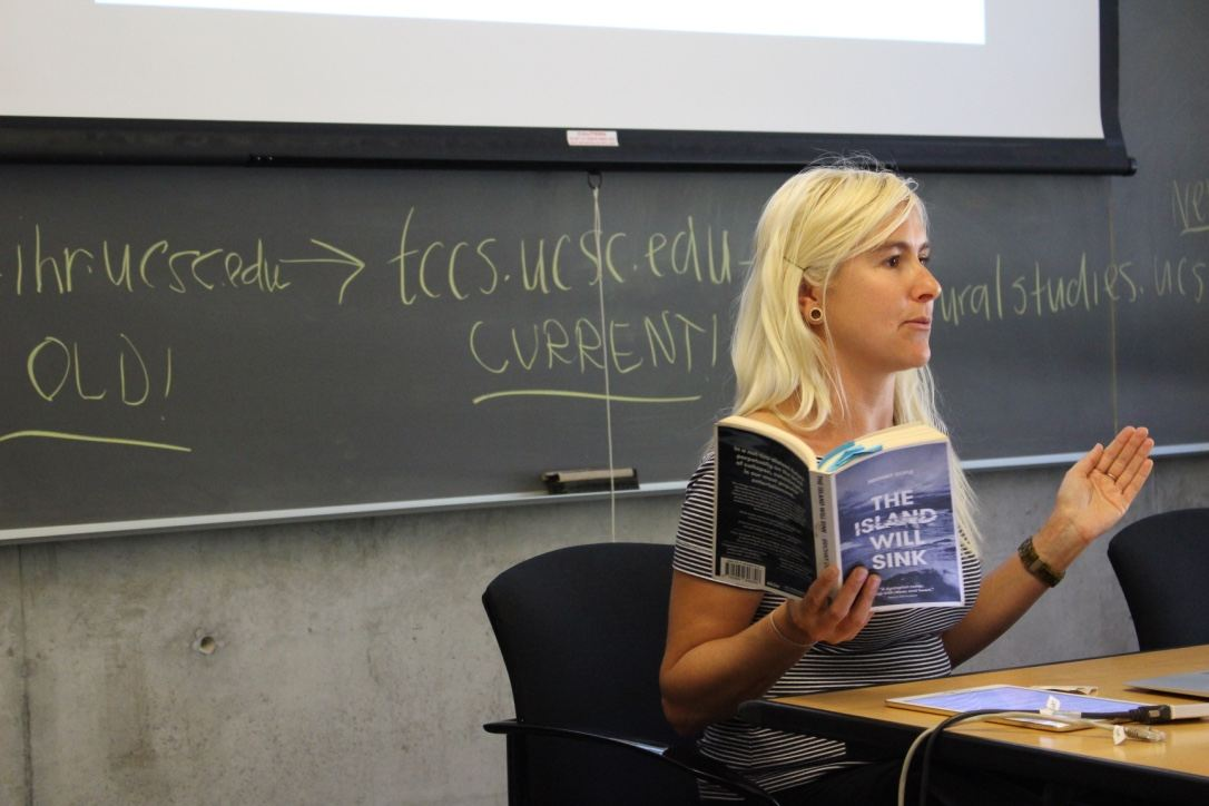 Briohny Doyle, seated, reads from her book. In the background, a chalkboard has writing on it.