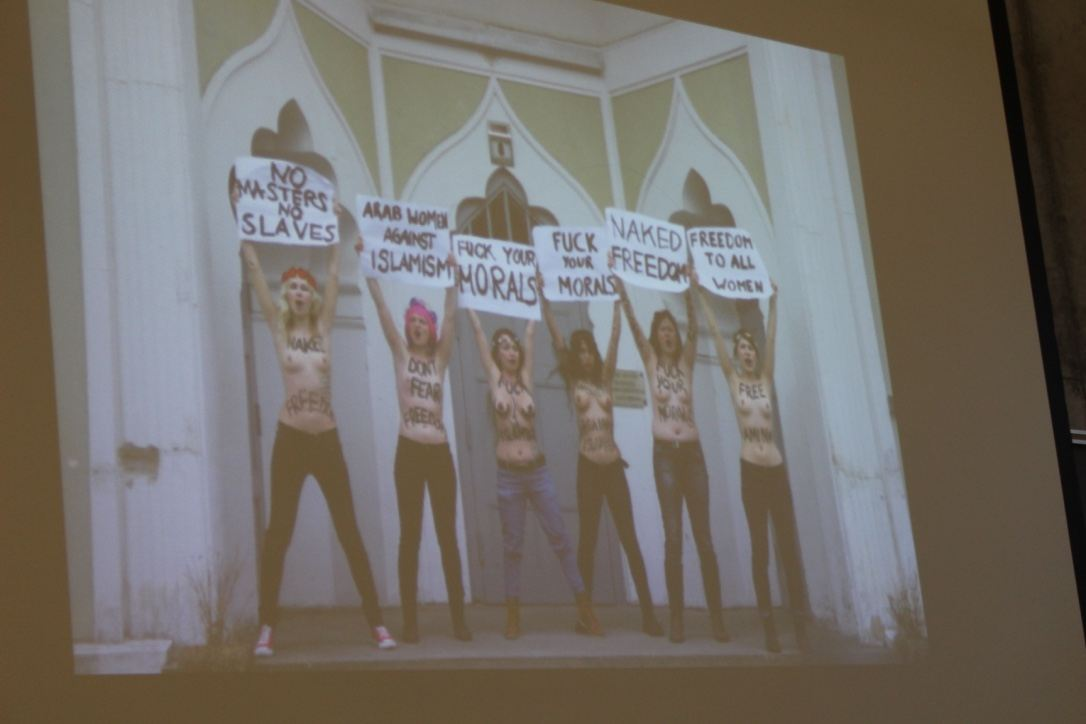 A photograph of a slide showing a photograph of several nude protestors holding signs, with feminist slogans written on their stomachs.