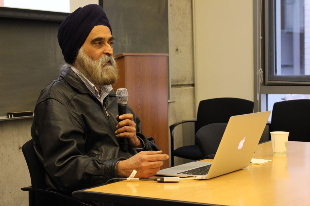 A man, wearing a turban, and holding a microphone, sits at a wooden table, beside a laptop.