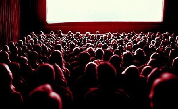 A crowded movie theatre shown from the back row.