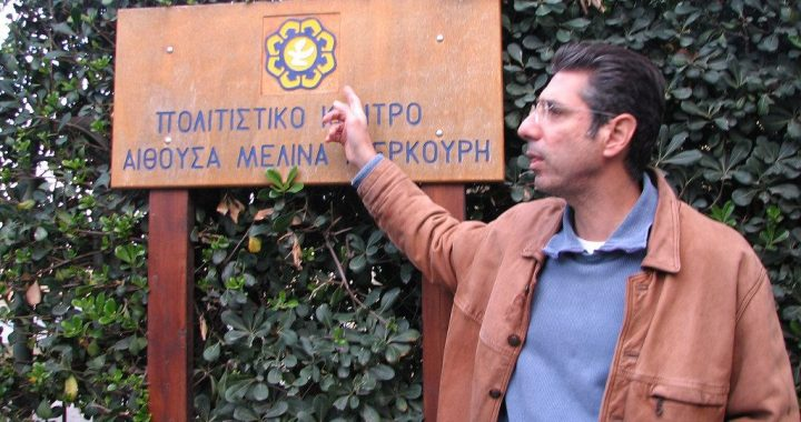 A man is shown from the waist up, pointing to a sign with Greek lettering.