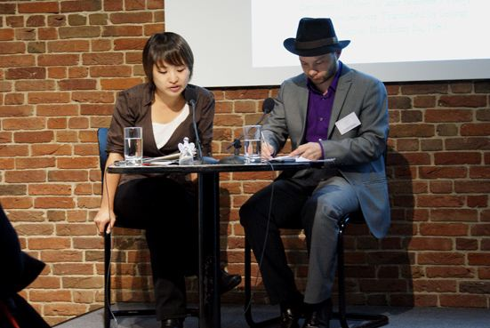 Two seated people are shown at a table, with a brick background.