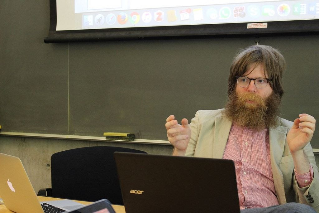 A bearded man wearing glasses sits in front of a computer screen, gesturing with his hands. Behind him, a chalkboard and the bottom of a screen