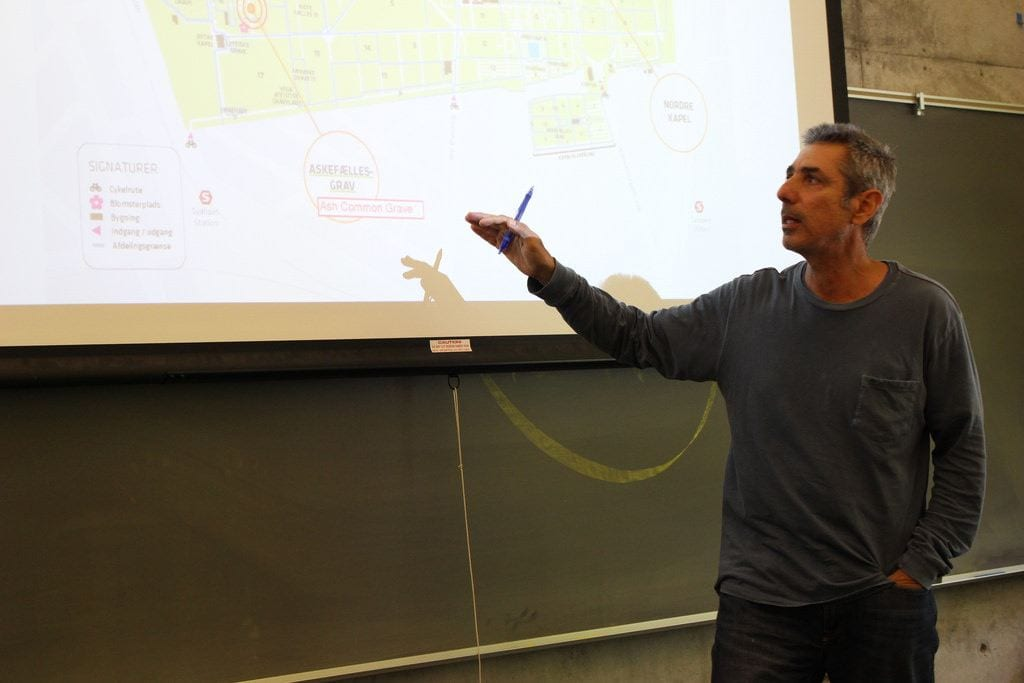 A man is shown in front of a projector screen, to which he points. On the screen is a map. Behind the screen, a chalkboard.