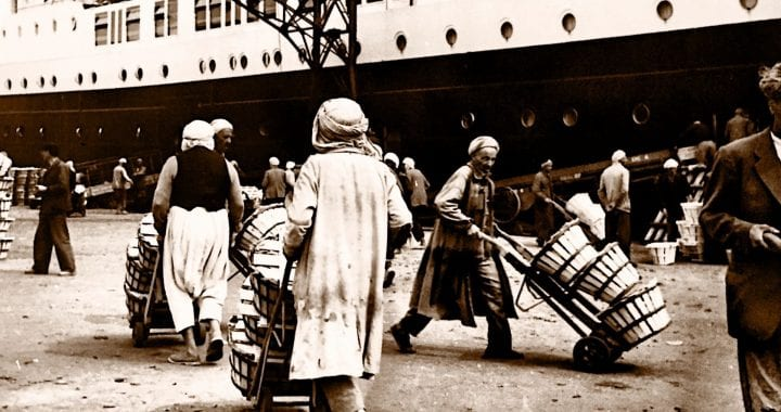 A black and white photo of men transporting goods in a shipping yard. A cargo ship is in the background.