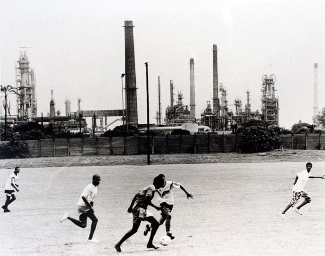 Black and white photo of five people playing soccer. In the background, the soccer field is bordered by a fence; beyond the fence are multiple industrial smokestacks.