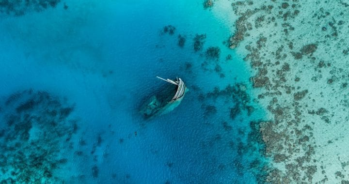 A photo taken from the sky of a sunken ship partially submerged in the ocean