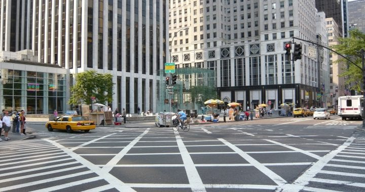 A photo of a crosswalk in New York City taken from a street corner. Vendors, pedestrians, and taxis line the street and sidewalk.