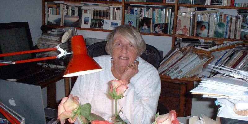 A photo of Helene Moglen sitting at her desk, resting her chin on one hand. A vase of flowers and a red reading lamp are in the foreground of the photo; a bookshelf filled with books is behind Helene.