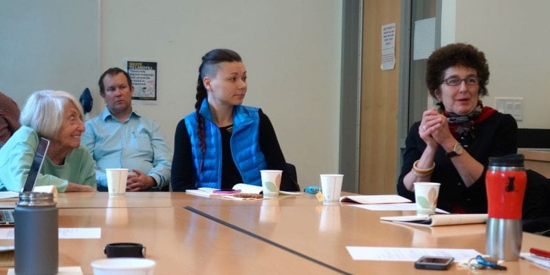 Three women at a table. Helene Moglen sits on the left, leaning forward and smiling while listening to Laurie Palmer, seated on the far right, talk. A woman in the middle also listens and faces Laurie